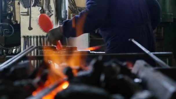 Smith cleans iron against fire