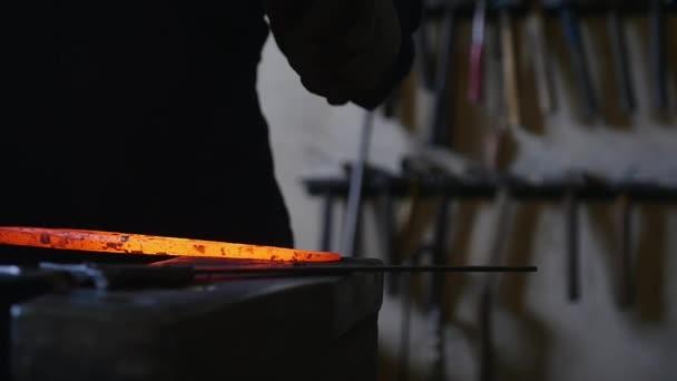Blacksmith bends an iron hot stick with a hammer