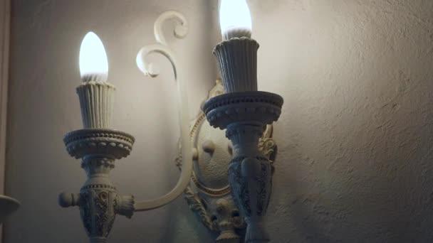 schöne moderne Beleuchtung an einer Wand mit Lampen in Form von Kerzen