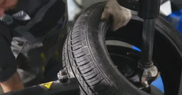 Profesionální auto mechanik nahradit pneumatiky na kolo v automatické opravy služby timelapse. Další mechanik vyvažování kol s vyvážením stroj, na servis
