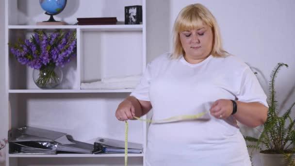 tlustá žena měří v pase a je spokojený