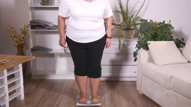 tlustá žena stojí na váze