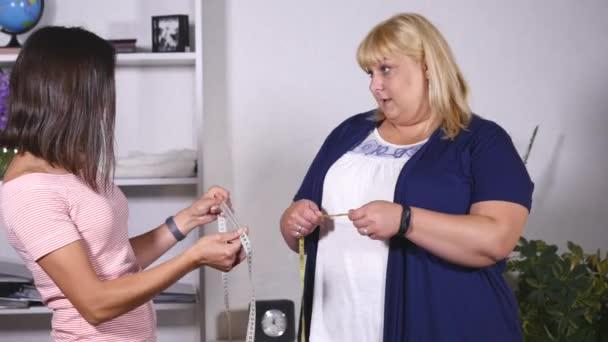 tlustá žena a tenké dívka měří jejich vlastní pas