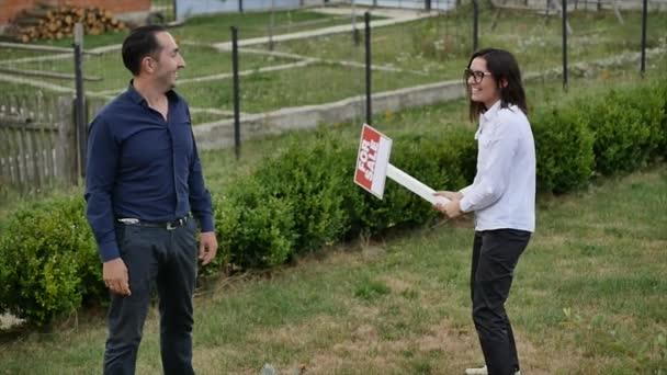 Paar mit Schild zum Verkauf