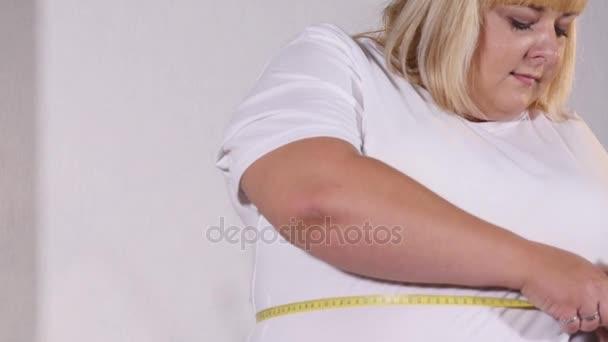 tlustá žena měří ji kolem pasu a jí hamburger