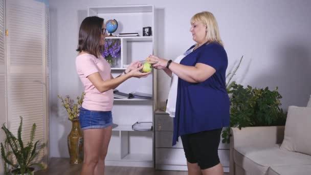 Tlustá žena a dívku vyměňovat jablko a burger