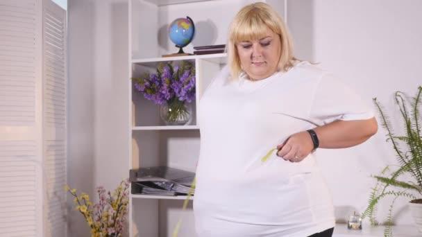 tlustá žena měří v pase a jí hamburger