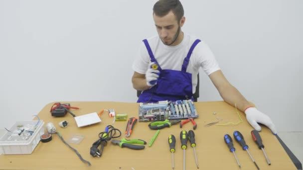 Servisman v modré pracovní oblek sedí pro pracovní stůl