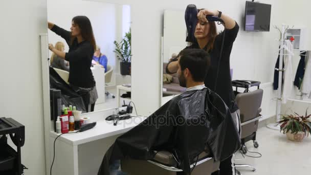 Professional hairdresser drying hair in beauty salon. Male young customer and female barber
