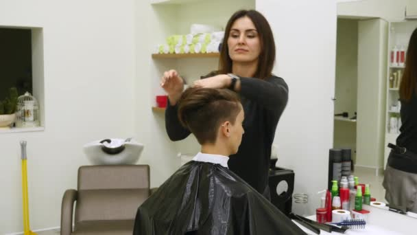 The womans hairdresser makes styling her hair on short hair