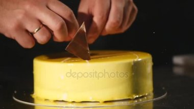 Details of cake. Chocolate and pretzels. Freshly cooked cake. Confectioner rotates the cake and decorate it. Yellow cream cake with chocolate icing, chocolate and pretzels. Confectioner decorate a