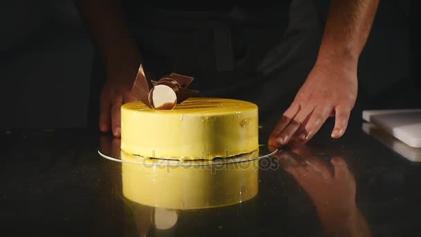 Details des Kuchens. Schokolade und Brezeln. frisch gekochter Kuchen. Konditor dreht den Kuchen und dekoriert ihn. gelbe Sahnetorte mit Schokoladenglasur, Schokolade und Brezeln. Konditor schmücken ein