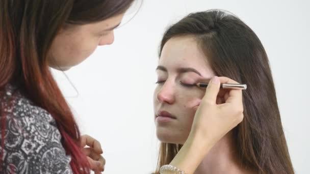 Professzionális sminkes alkalmazása szemhéjfesték modell szem speciális kefe segítségével. Természetes smink a szalonban. Szépség, smink és divat fogalma
