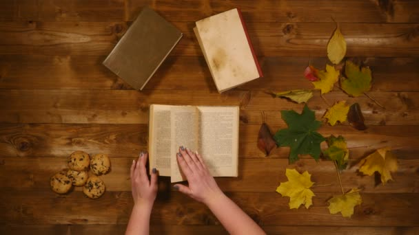 Herbst Konzept Draufsicht. Bücher, Ahornblätter, backen die alten Holztisch. Frau blättert durch die Seiten des Buchs