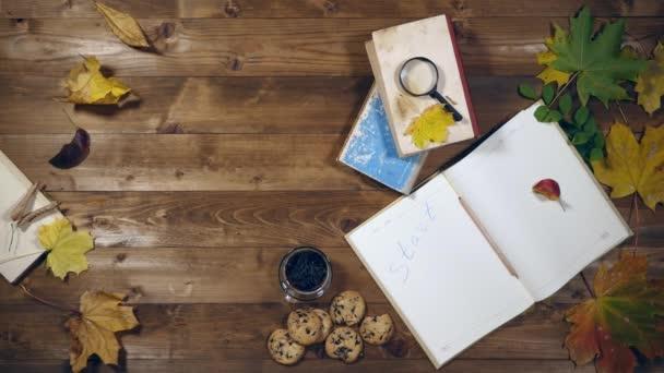 Podzimní pohled shora koncept. Knihy, javorové listy, čaj na starý dřevěný stůl. Žena, psát poznámky v tomto poznámkovém bloku