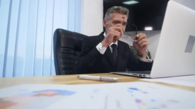 Businessman having head pain during work in office