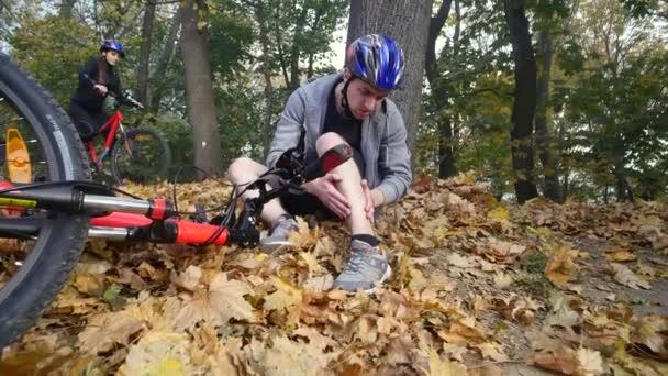 Mladý muž sedí v parku po pádu z kola, zklidňuje bolesti v koleni, je nebezpečné kolo Jízda v parku na podzimní den