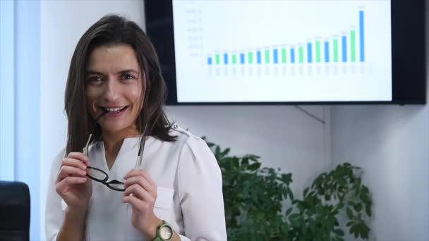 Jistý zralá podnikatelka v úřadu. Ženské manažer v kanceláři při pohledu na fotoaparát a usmívá se. Zpomalený pohyb