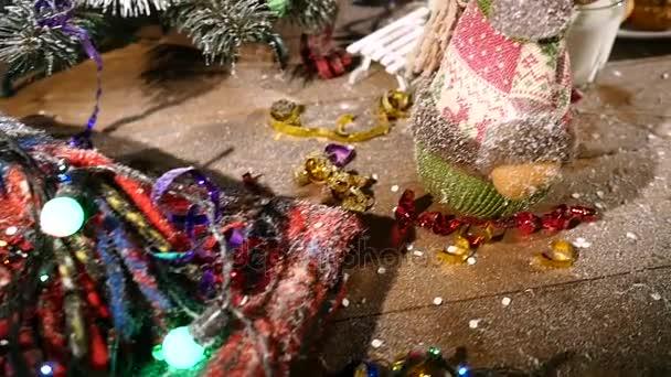 Dřevěný hnědý stůl zdobený vánoční věci a girlandy. Sklenice mléka a talíř cookies na vánoční stůl