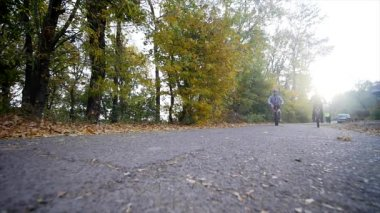 A woman and a man riding a bike an autumn day. sunlight background. slow motion