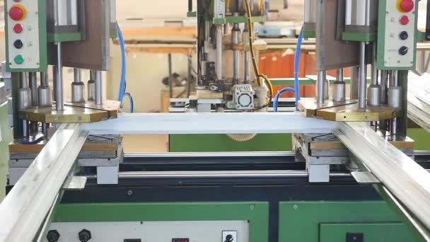 Moderní dílny pro výrobu plastových a kovových oken a dveří s profesionální specializované zařízení. Řádek výroby plastových oken. Plastové okenní rámy pohybovat podél výrobní linky