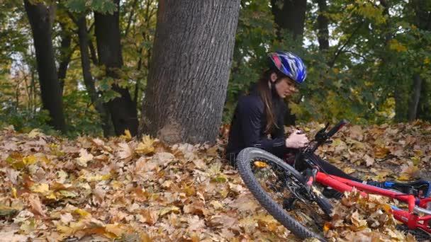 Mladá žena sedí v parku po pádu z kola, zklidňuje bolesti v kolenou, je nebezpečné kolo Jízda v parku na podzimní den