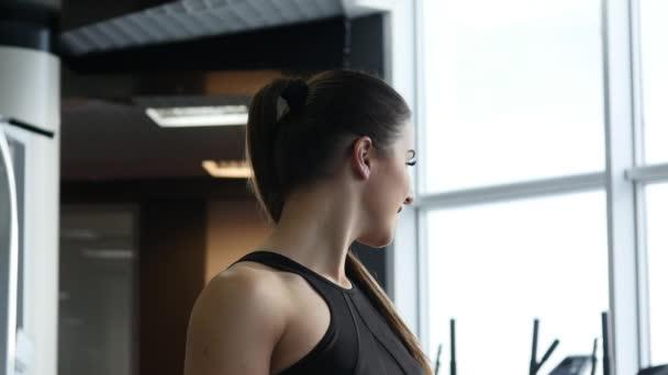 Sportovní krásná žena, která dělá fitness cvičení v tělocvičně pozadí zůstat fit. Fitness cvičení motivace