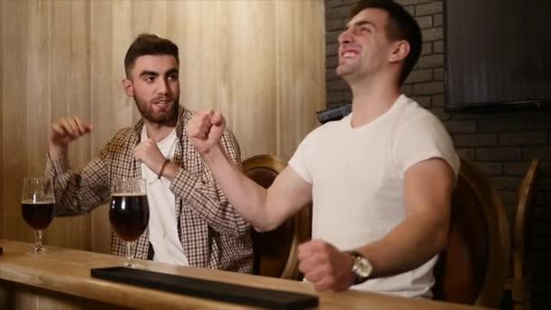 Két fiatal férfi meg ül a bárban, és beszél egymással, miközben ivott sört