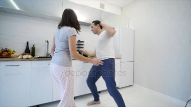 Morning at home happy young couple newly wed dancing listening to music in kitchen wearing pajamas. slow motion