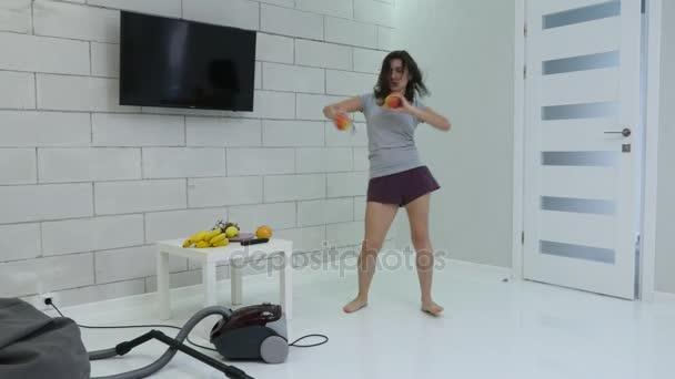 ein junges Mädchen putzt mit einem Staubsauger das Haus und tanzt