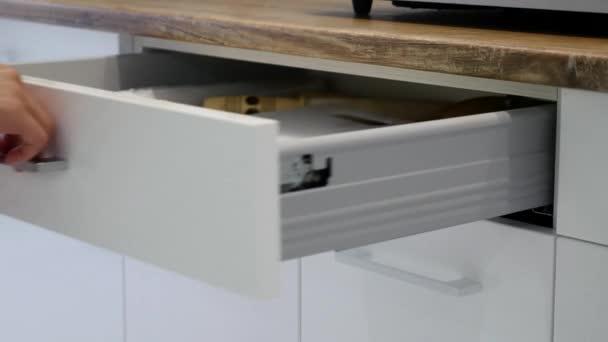 Frau Hand Öffnung Schubladen a weißer Küchenschrank