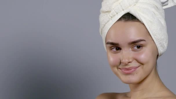 Beauty woman with a towel on her head moving her head and smiling
