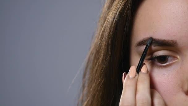una bella giovane donna pettine suo sopracciglio. Bella donna disegnare la forma delle sopracciglia utilizzando pennello cosmetico di bellezza. Chiuda in su