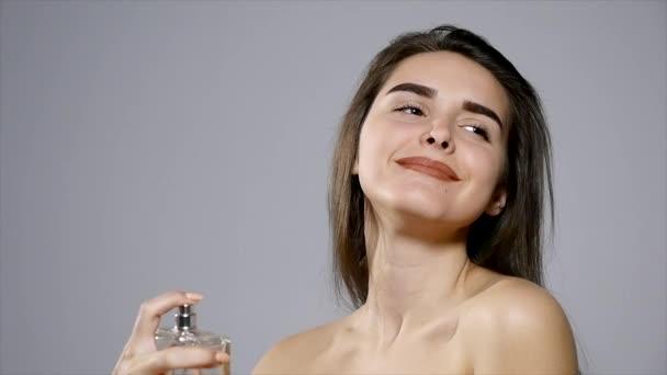 cute girl spraying some perfume on her body
