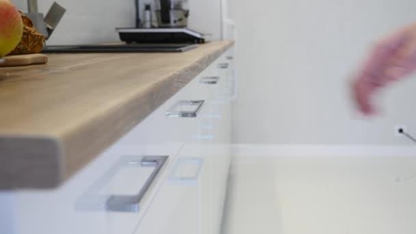 Ženská ruka otvírat zásuvky a bílé kuchyňské skříňky