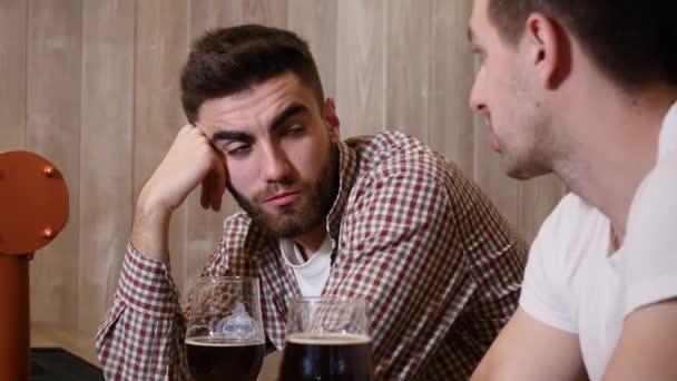Két fiatal férfi meg ül a bárban, és beszél egymással, miközben ivott sört.