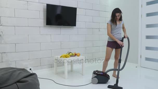 Ein junges Mädchen putzt mit einem Staubsauger das Haus