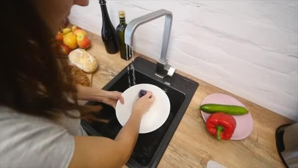 Junge hübsche Frau waschen Geschirr in der modernen Küche