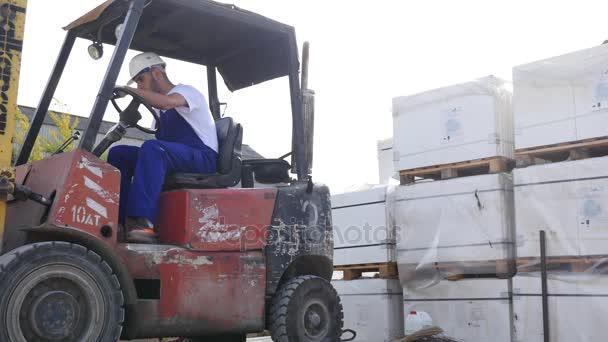 targonca vezető, egy gyár vagy raktár vezetői között sor polcok és halom dobozok és csomagolóanyagok