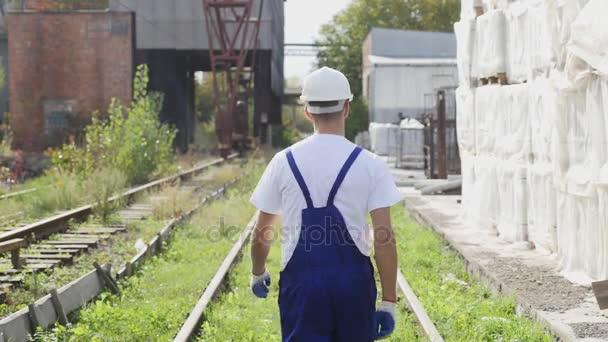 Železniční dělník v bílou helmu pěšky podél železnice