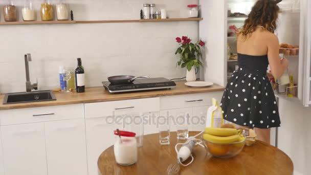 Mladá žena připravuje těsto míchání ingrediencí míse pomocí metly v kuchyni. Domácí jídlo. Slowmotion shot