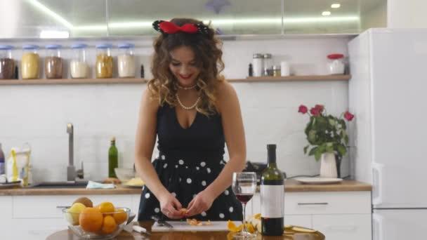 Žena řezy jako mandarinku na dřevěné desce kuchyně v domácí kuchyni. Vaření potravin v domácnosti. Domácí atmosféru v kuchyni