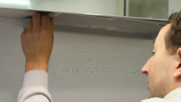 Muž se kroutí šroub šroubovákem. Shromažďuje nábytek