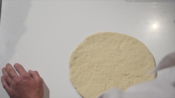 Koch Verbreitung Tomatensauce auf Pizzateig mit einem Metall Schöpflöffel in Pizzeria