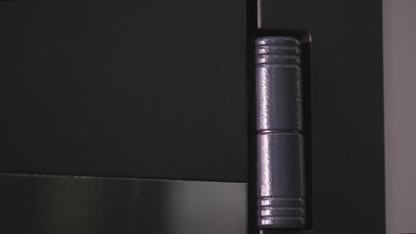 rostfreie Scharniere auf einem schwarzen Tor