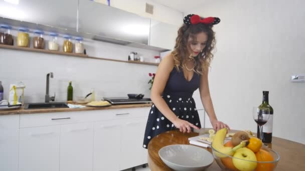 Woman Slices a Banana on a Wooden Kitchen Board in a Home Kitchen. Cooking food at home. Home atmosphere in the kitchen