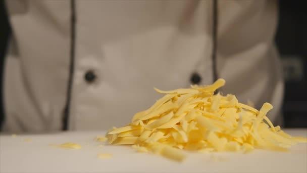Kuchař tře sýr na struhadlo