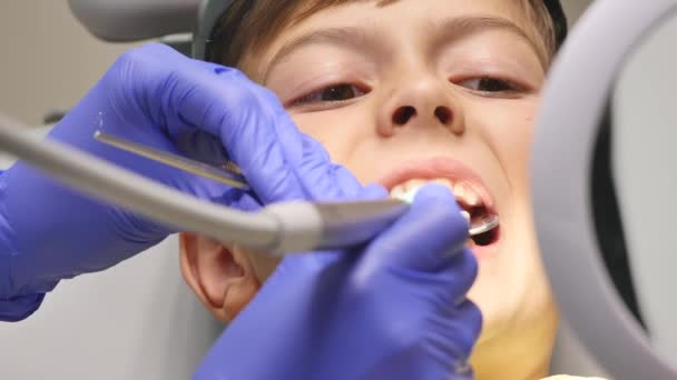 Closeup little kid during procedure of teeth drilling treatment at dentist clinic office