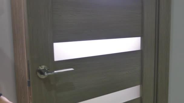 Muž otevřel dveře a vejde do místnosti