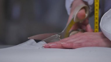 Woman cutting a piece of cloth at table in fashion studio.